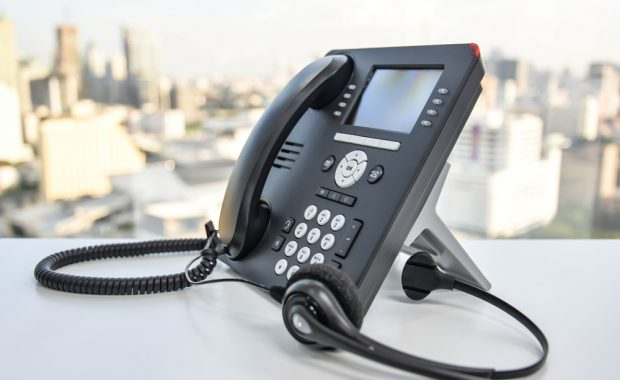 black office phone and headset with city skyline background